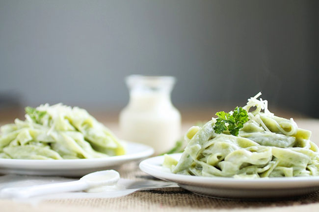 Two white plates filled with spinach fettuccine and topped with fresh parsley.