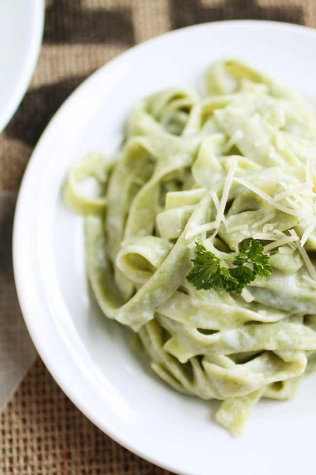 Spinach fettuccine topped with a sprig of fresh parsley.