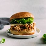 Shredded barbecue chicken on a sandwich roll with cheese and lettuce.