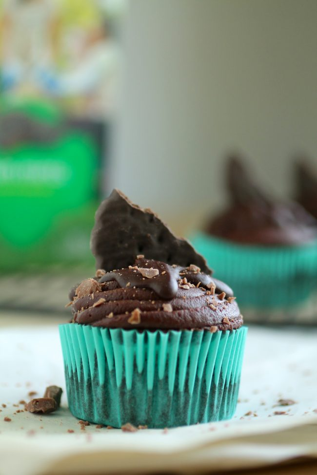 Chocolate cupcake in front of a box of thin mint girl scout cookies.