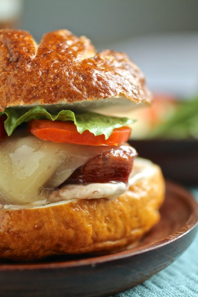 Close up of the sandwich to show layers of chicken, sauce, tomato, cheese, and lettuce.