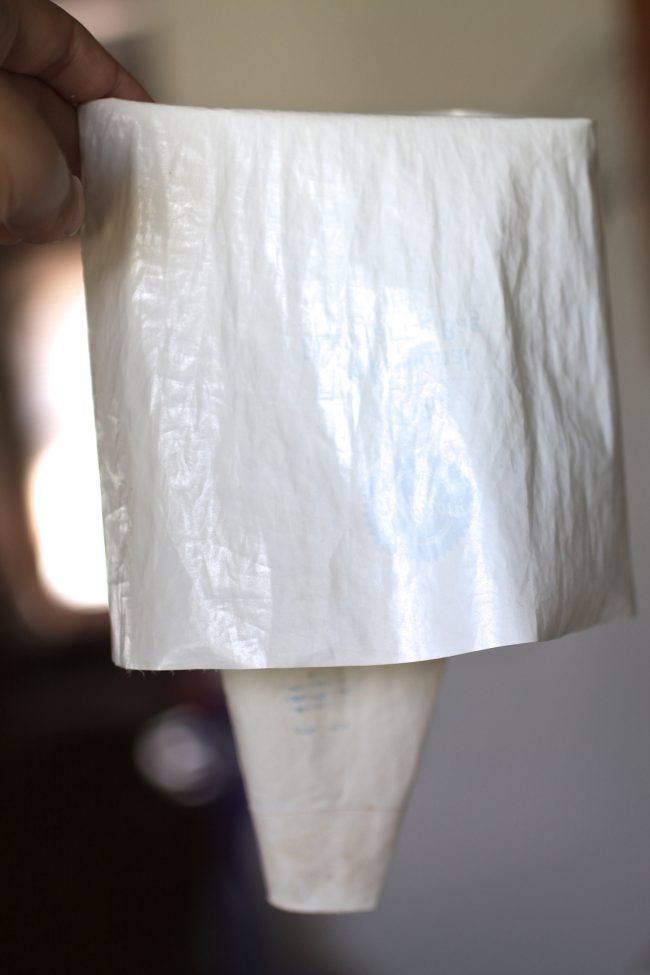 Hand holding a white pastry bag, with the top third of the bag folded down to make it easier to fill.
