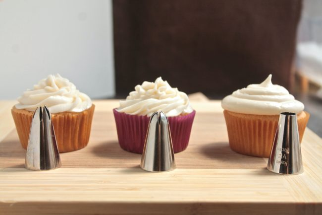 Three frosting tips, each sitting in front of a cupcake they have frosted to show the difference in texture.