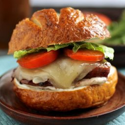 Chicken on a pretzel roll with tomatoes and lettuce.