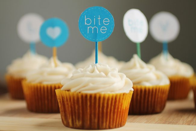 Vanilla cupcake with a blue toothpick in the center. The toothpick holds a small tag that says \'bite me.\'