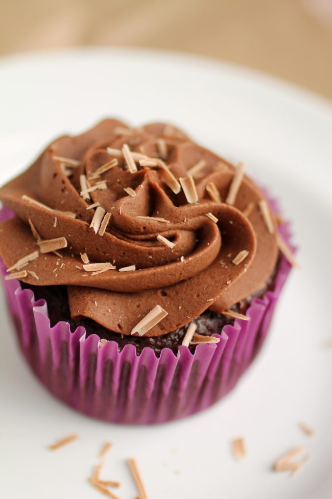 Chocolate cupcake with chocolate buttercream topped with chocolate shavings.