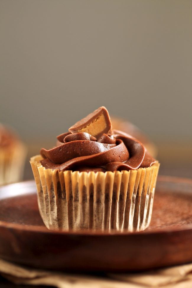 Chocolate cupcake topped with half a peanut butter cup.
