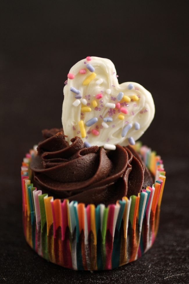 Chocolate cupcake topped with a white chocolate heart.