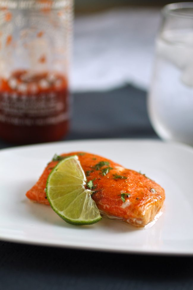 Slice of salmon on a white plate next to a lime wedge, in front of a bottle of sriracha.