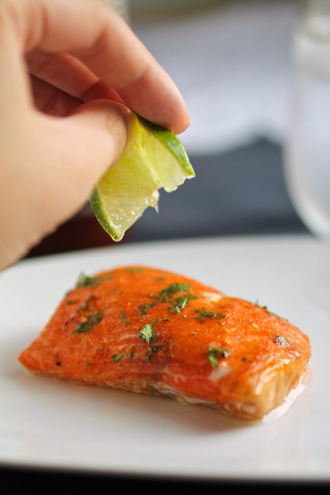 Hand squeezing a lime wedge over a piece of salmon.