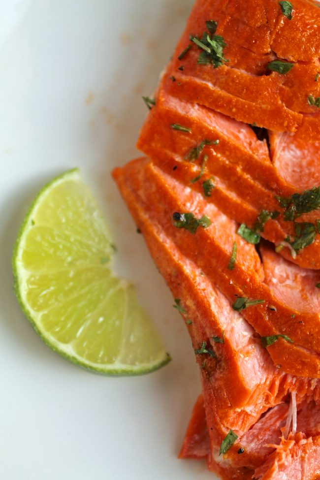 Flaked salmon next to a lime wedge.