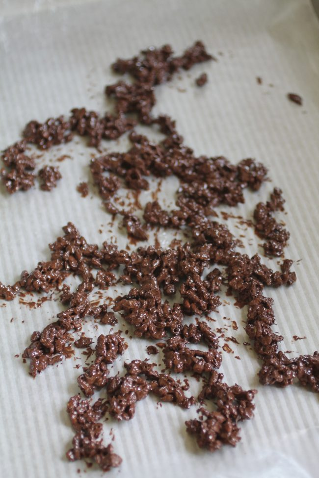 Chocolate and puffed rice cereal drying on a piece of waxed paper.