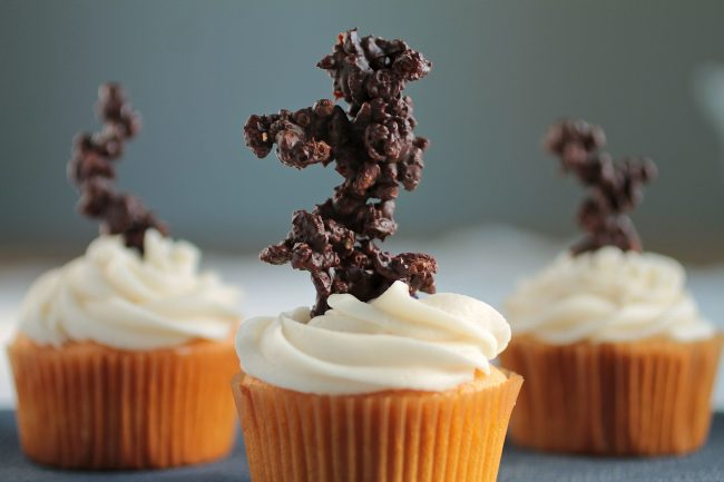 Cupcake with white frosting and a chocolate decoration on top.