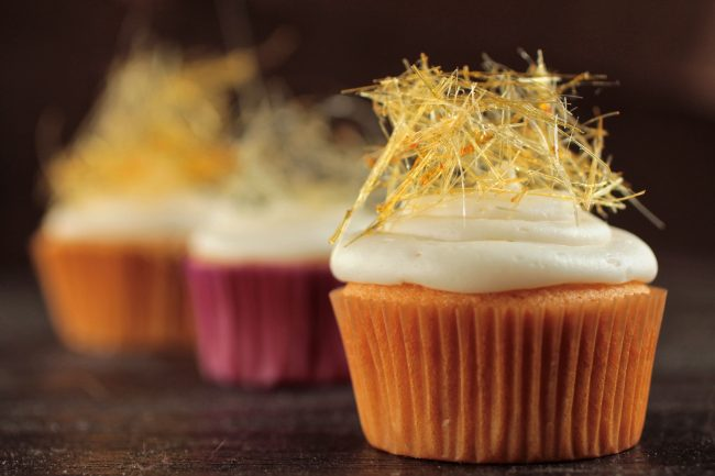 Three cupcakes with vanilla frosting, topped with a small nest of thin sugar strands.