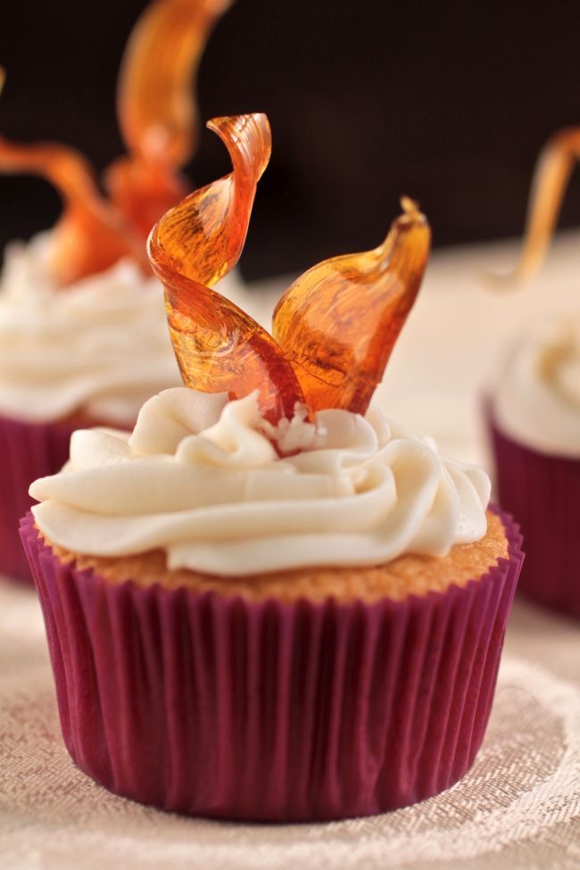 Vanilla cupcake with white frosting topped with a golden brown sugar ribbon.