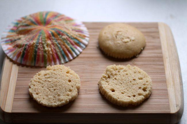 A vanilla cupcake, sliced horizontally into three round pieces.