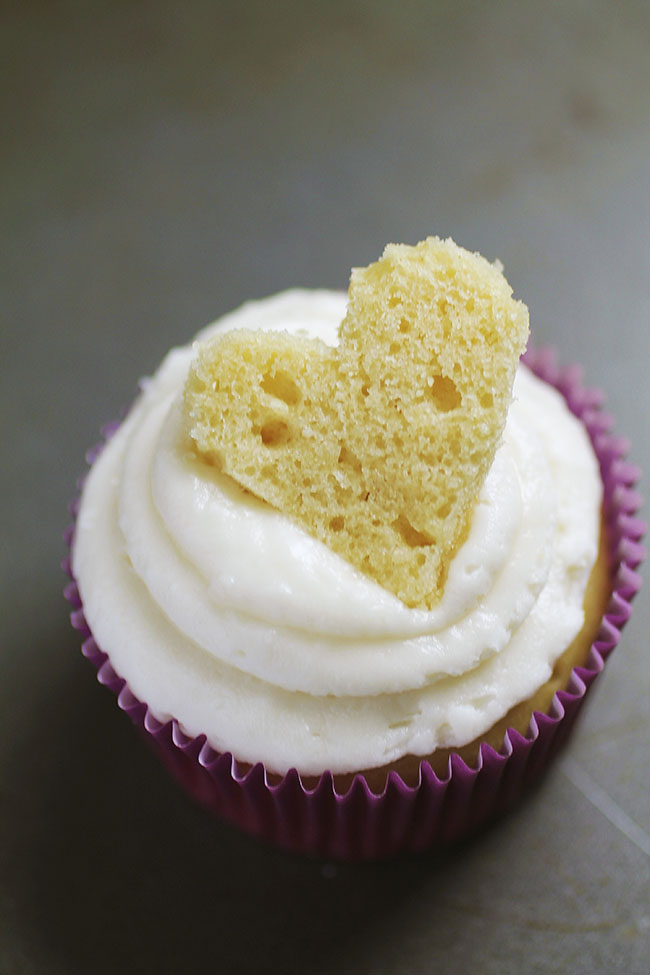Vanilla cupcake topped with a piece of cake cut into the shape of a heart.