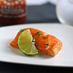 Slice of salmon on a white plate next to a lime wedge.