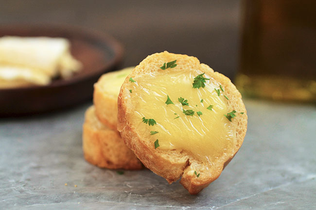 Close up of crostini topped with melted brie and fresh parsley.
