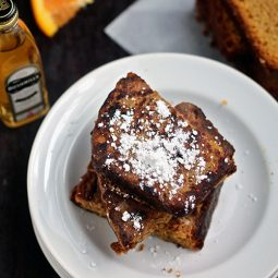 Two slices of french toast stacked on a white plate.