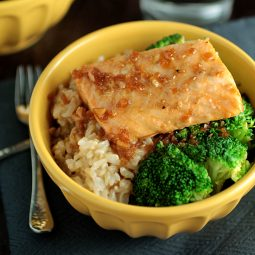 Yellow bowl filled with rice, broccoli, and roasted salmon.