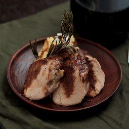 Pork tenderloin slices on a wooden plate.