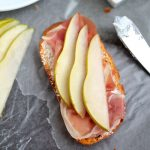 overhead photo of sliced pears and prosciutto on top of a piece of crostini