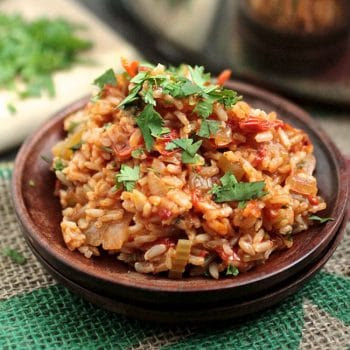 Jambalaya topped with fresh cilantro on a small wooden plate.