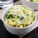 Tortellini in a white bowl topped with parmesan cheese.