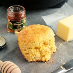 Biscuit next to a stick of butter and a small jar of honey.