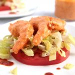 Shrimp with remoulade sauce on top of a tomato slice.