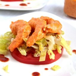 Shrimp remoulade on top of a sliced tomato and a handful of lettuce.
