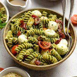 Pasta salad in a brown bowl with two serving spoons tucked into the side.