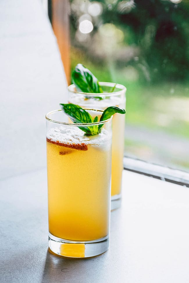 Tall gold rimmed drinking glasses filled with peach bourbon cocktail, sitting in front of a window, with a fresh basil garnish.