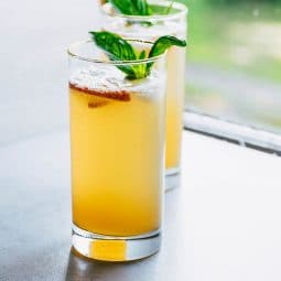 A peach bourbon cocktail with a sprig of fresh basil, in a tall glass by a window.