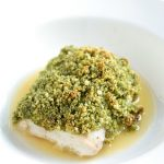 Mahi Mahi topped with pesto and breadcrumbs, sitting in a pool of butter sauce.
