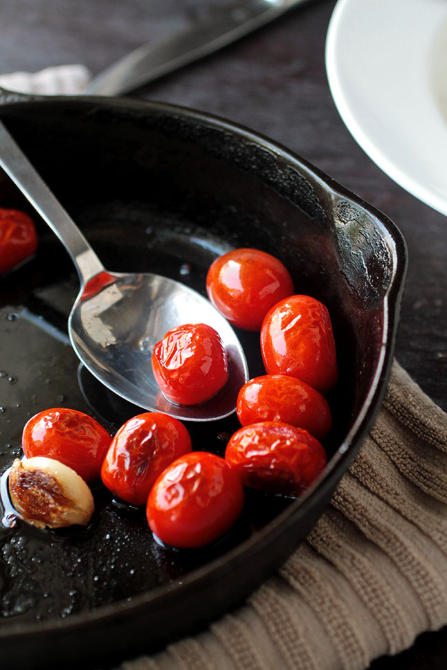 Spoon stirring blistered tomatoes in a cast iron skillet.