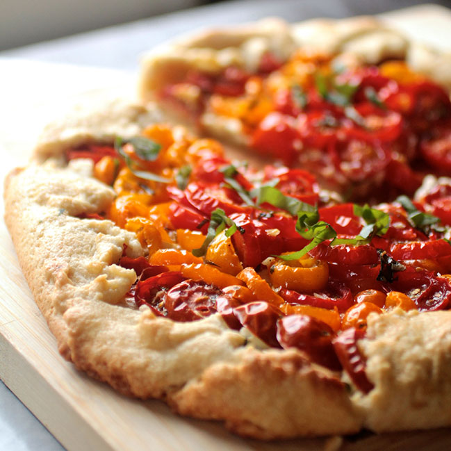 Tomato galette on a wooden cutting board next to a window