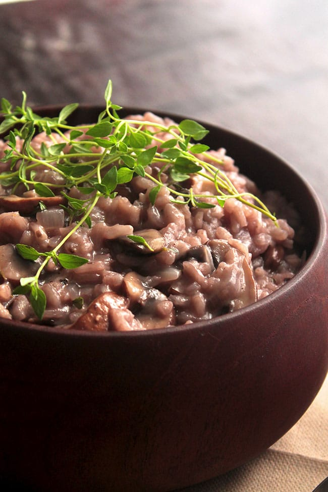 Dark wooden bowl on a brown background filled with light red mushroom risotto and garnished with fresh thyme.