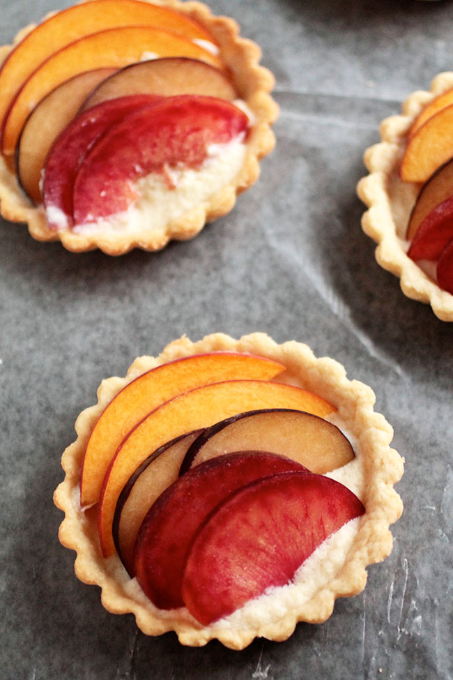 Three small tartlets on a piece of parchment paper.