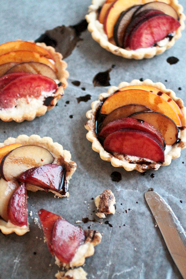 Three small tart shells topped with stone fruit on a light background.