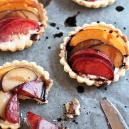 Three stone fruit tartlets topped with plum and peach slices.