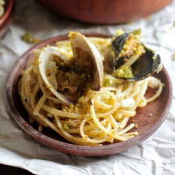 Wooden plate filled with spaghetti, topped with clams and mussels.