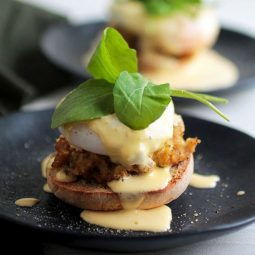 Crabcake eggs benedict on a navy plate, topped with fresh arugula.