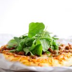 Small pizza topped with fresh arugula on a white table.