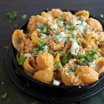 A small cast iron skillet filled with shell pasta, topped with blue cheese and fresh parsley.