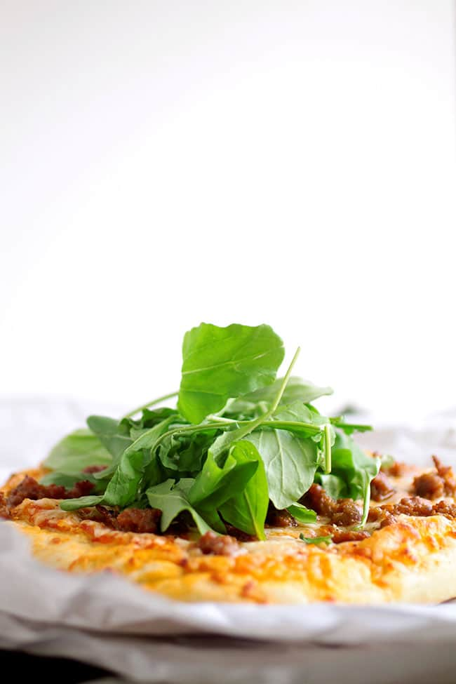 Close up of pizza topped with fresh arugula in front of a white background.