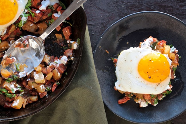 Large spoon in a cast iron skillet with breakfast hash, next to a small plate with a fried egg.