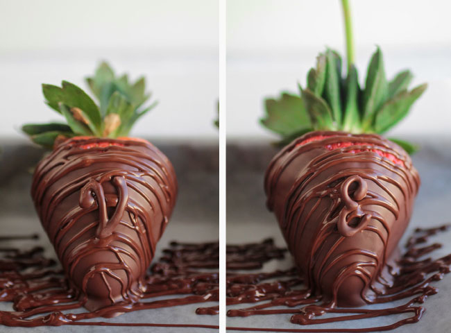 Two chocolate covered strawberries on a piece of parchment paper with melted chocolate drizzled on top