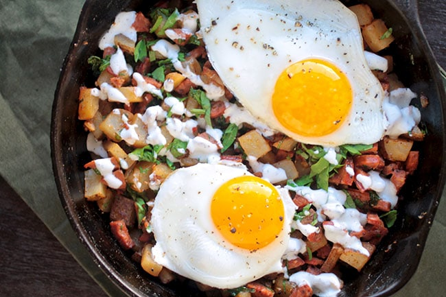 An easy breakfast hash recipe with chorizo sausage, potatoes, arugula, and a homemade lime crema. Topped with overeasy eggs for a tasty brunch recipe.
